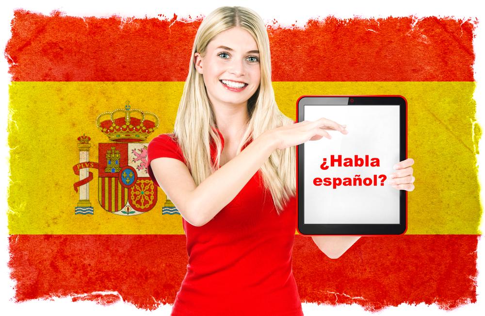 תרגום לספרדית בתמונה אישה צעירה, מחזיקה מחשב לוח ברקע דגל ספרד ברקע