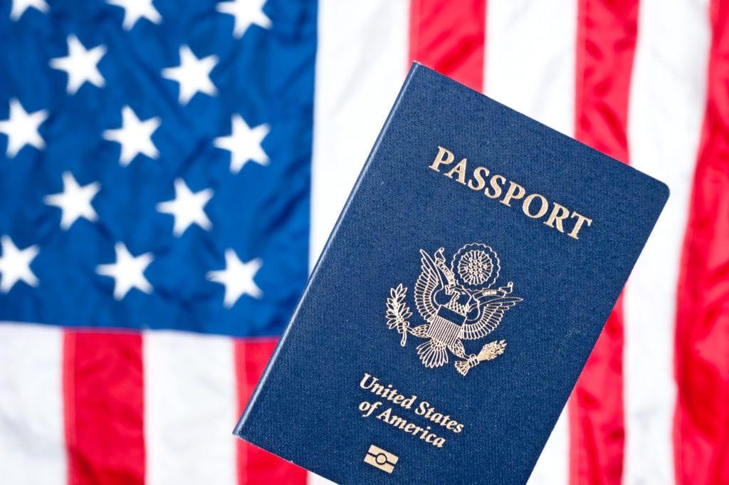 תרגום תעודות ומסמכי הגירה בתמונה דרכון על רקע דגל ארצות הברית