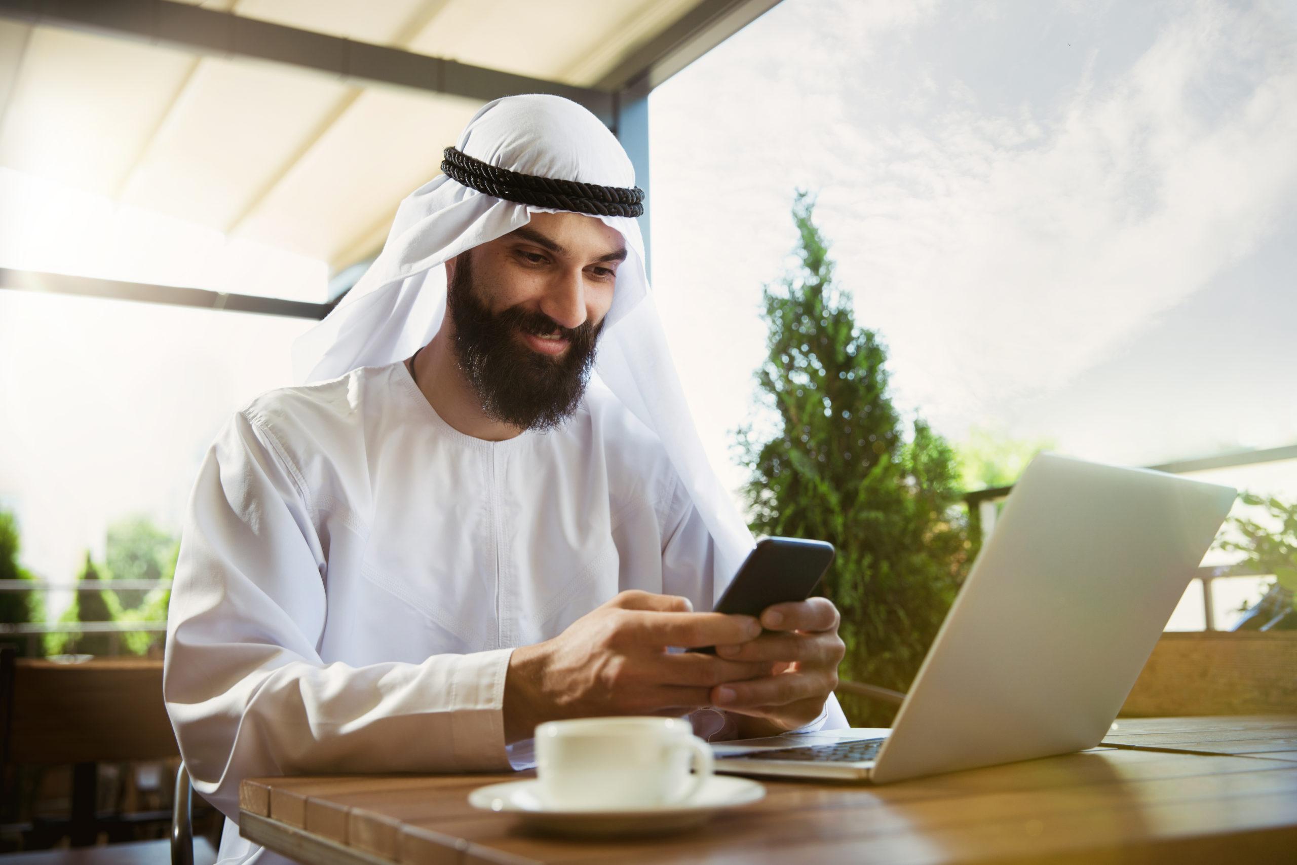 תרגום לערבית: בתמונה איש עסקים לובש כפיה לבנה ליד מחשב מקיש לסלולרי