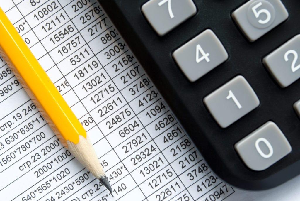 תרגום דוחות כספיים לאנגלית בתמונה: מחשבון ועיפרון צהוב מונחים על דף מספרים