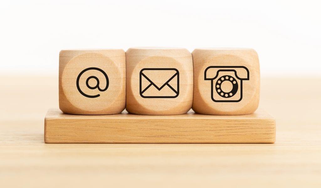 צור קשר לקבלת שירותי תרגום  בתמונה סמל טלפון. שטרודל וסמל מעטפה על קוביות עץ