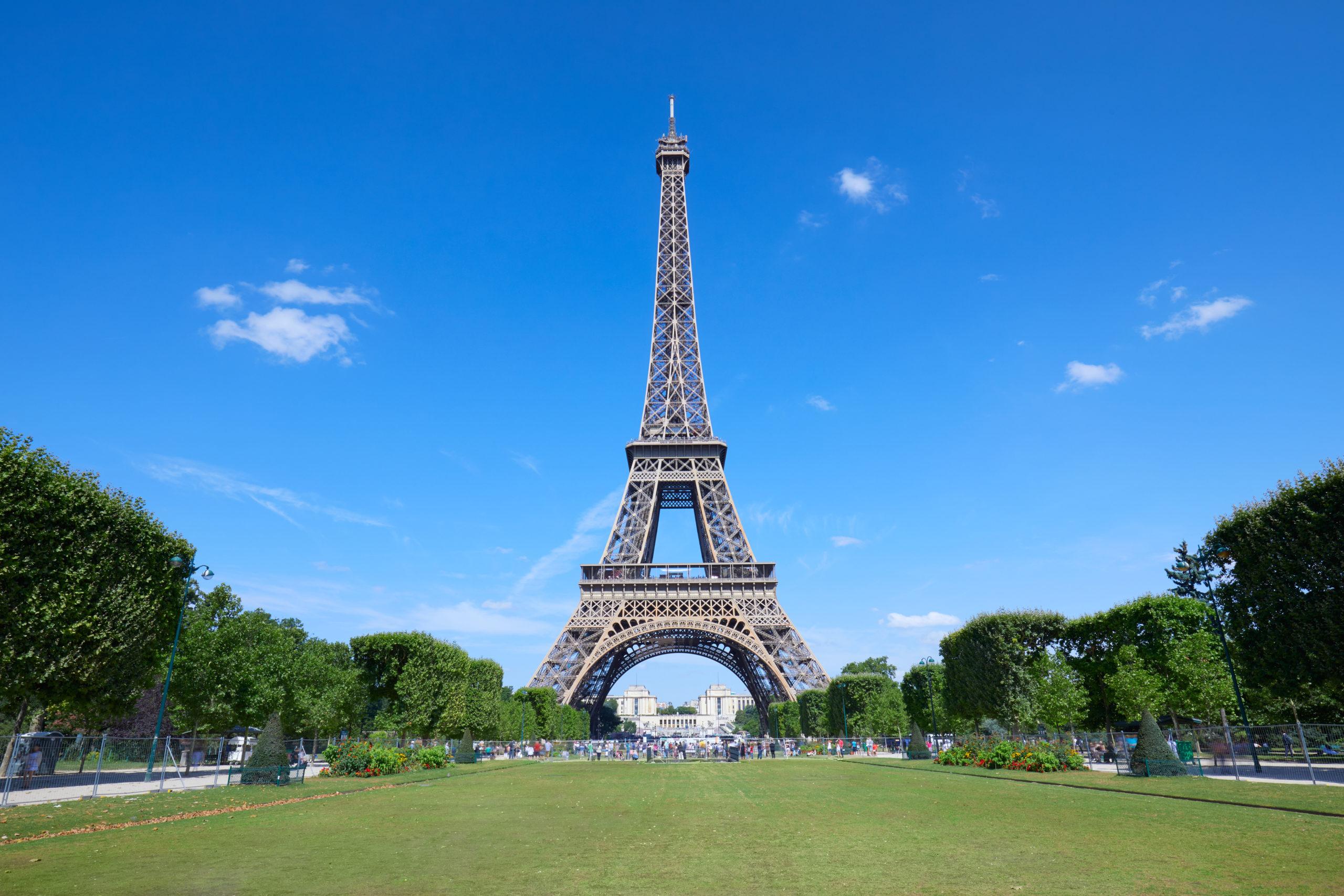 תרגום מסמכים לצרפתית בתמונה: -מגדל אייפל בפריס ושדה ירוק שמיים כחולים בהירים