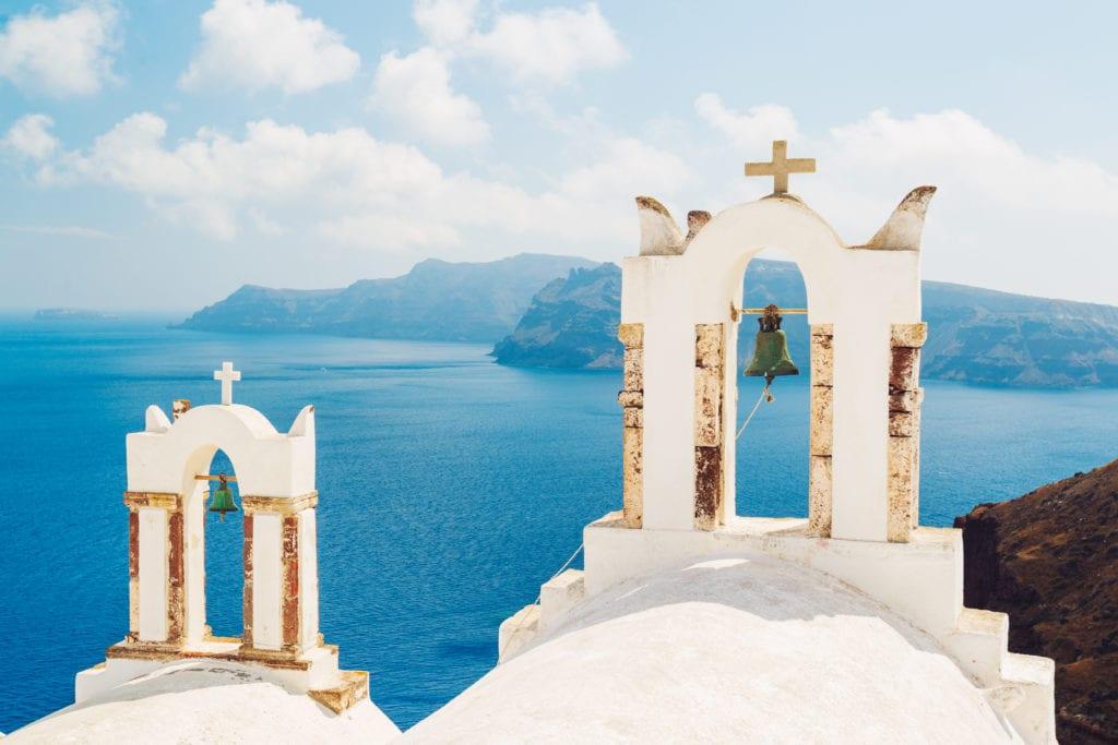 תרגום מסמכים ליוונית בתמונה אדריכלות יוונית בניינים לבנים  פעמון על רקע ים כחול, באי סנטוריני, יוון